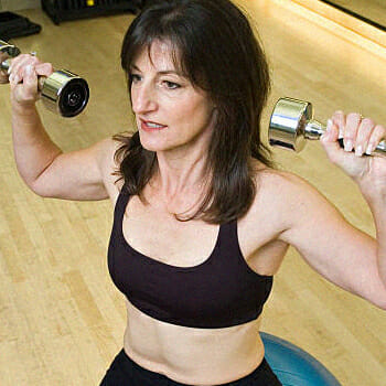 Middle aged woman doing overhead press workout