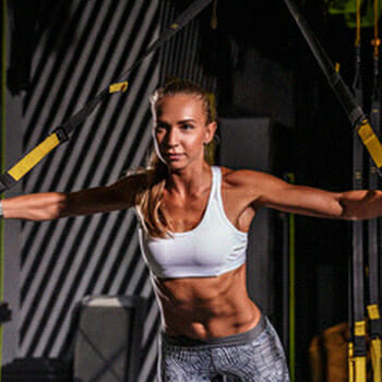 A fit woman doing the TRX Chest fly exercise