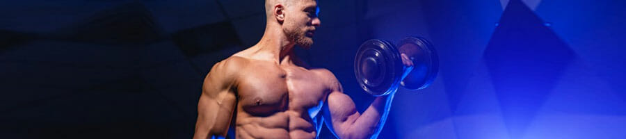 shirtless man using a dumbbell on one arm
