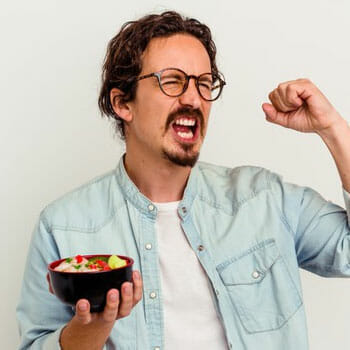 man in joy holding up a bowl of meal