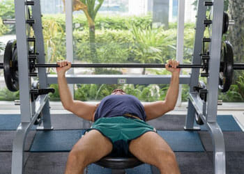 man laying down on a bench press