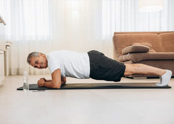 man in a plank position on a yoga mat
