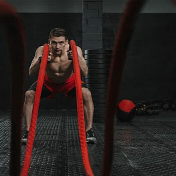 shirtless man doing high intensity workout with a rope