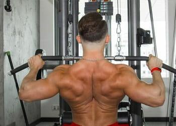 man using a lat machine shirtless