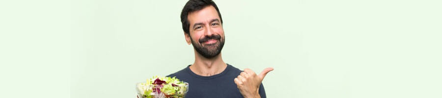 man smiling holding a salad bowl and a thumbs up