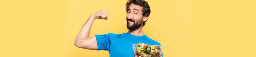 man flexing his biceps while holding a bowl of salad