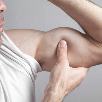 man flexing and squeezing his biceps using his hands