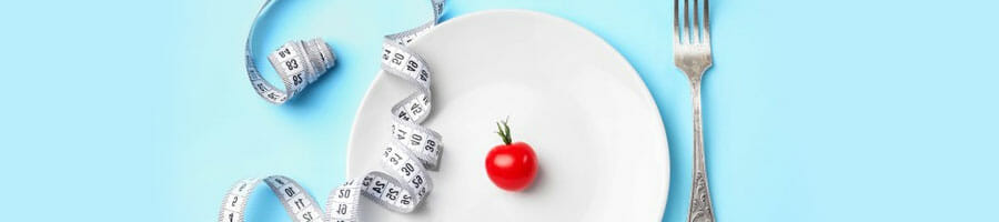 measuring tape and tomato on a plate with a fork beside
