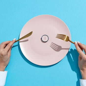 plate with small clock on it and a person holding knife and fork