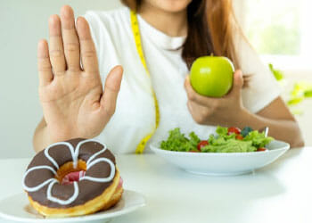 woman holding an apple while saying no to donuts
