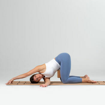 woman in a thread the needle pose in a yoga mat