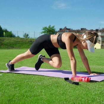 woman working out with a yoga mat outdoors
