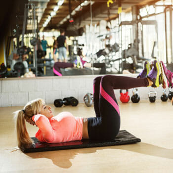 woman in a reverse crunch position in a gym