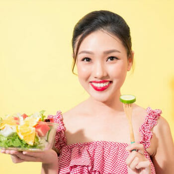 woman holding up a salad bowl and a fork