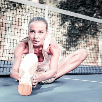 woman doing a seated leg stretch outdoors