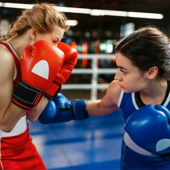 two women boxing in a ring gym