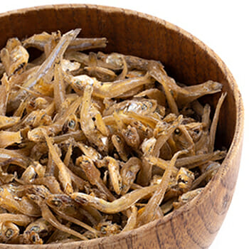 Dried anchovies fish in a wooden bowl