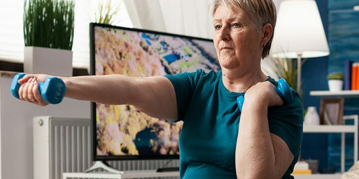 Woman watching aeorobic workout using tablet sitting swiss ball