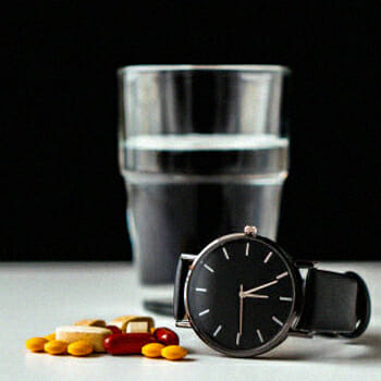 A watch, a glass of water and different supplements on a table