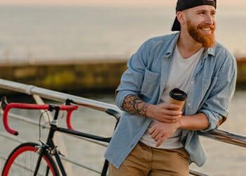 A man relaxing near a bridge beside his bike while holding a coffee