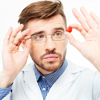 medical person holding up a pill while looking at it