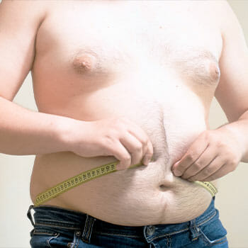 shirtless man with big belly measuring his waist
