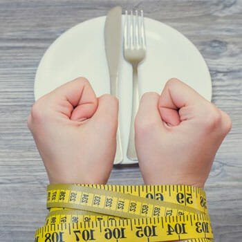 empty plate on a table and a person hand tied in a measuring tape