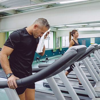 man wiping sweat while on treadmill