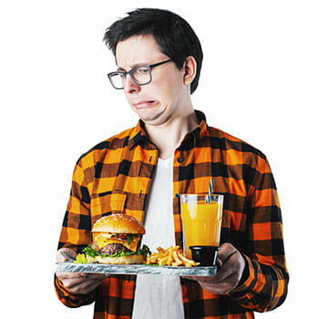 man holding a tray of junk food with a grossed out face