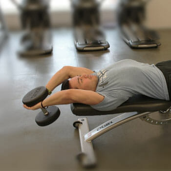 man in a dumbbell pullover position in a gym