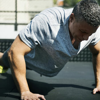 man in a plank position doing burpees