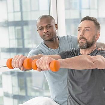 trainer assisting a man lifting dumbbells
