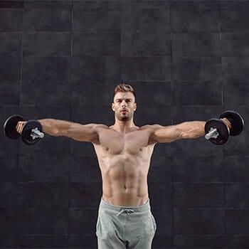 shirtless man raising dumbbells on both arms