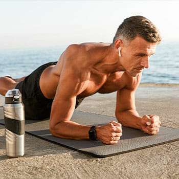 shirtless man in a plank position outdoors