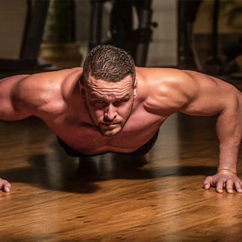 shirtless man in a push up position