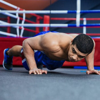 shirtless man in a push up position in a gym