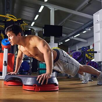 shirtless man doing pushups on a platform