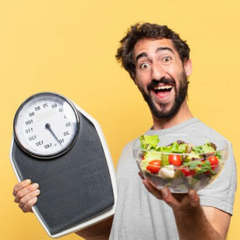 smiling bearded man holding up a salad bowl and a weighing scale