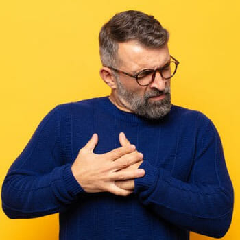 aged man with both of his hands in his chest in pain