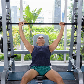 man in a gym doing bench presses