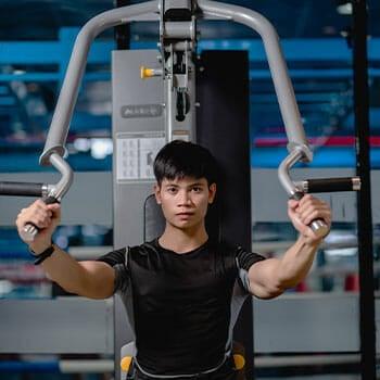 man using a pec deck machine in a gym