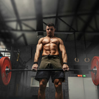 shirtless man weightlifting a heavy barbell