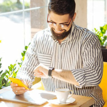 man sitting in a cafe looking at his watch while holding his phone