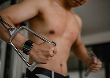 close image of shirtless man's hand gripping a cable machine