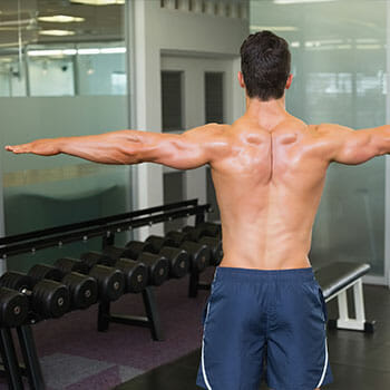 shirtless man showing his back while both arms are raised