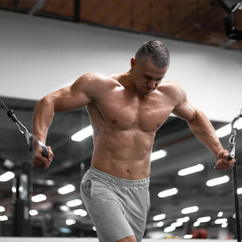 shirtless man doing standing cable flys