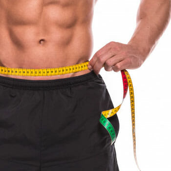 shirtless man with abs wrapping his belly with measuring tape