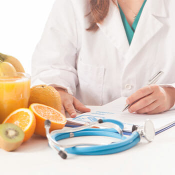 table view of a nutritionist writing with fruits on the side