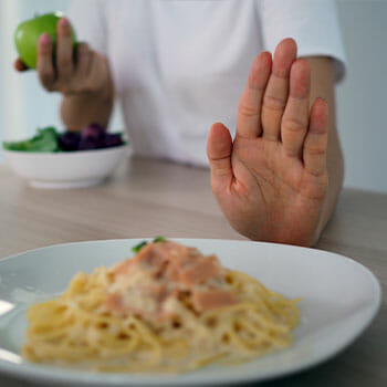 person's hand shoving away a pasta plate