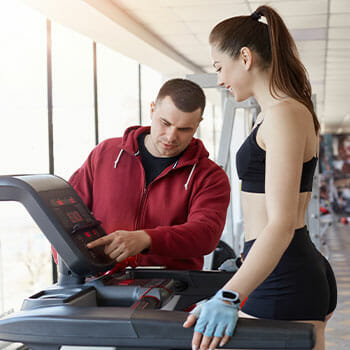 gym instructor teaching a woman how to use a treadmill